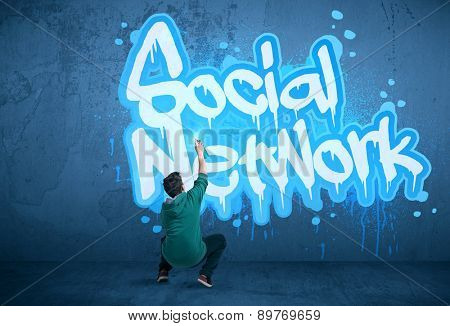 Young urban painter drawing a social network subtitle on the wall