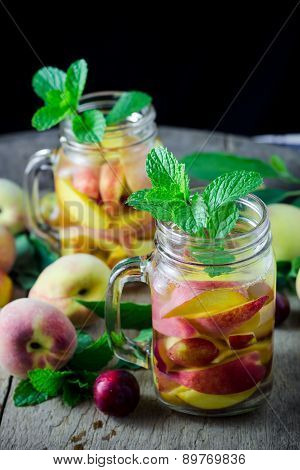 Jar Delicious Refreshing Drink Of Peach Fruits And Plum  With Mint On Wooden