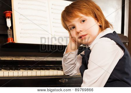 Girl holds her face with hand on the piano