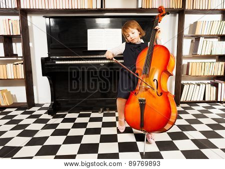 Beautiful girl in school dress playing on cello