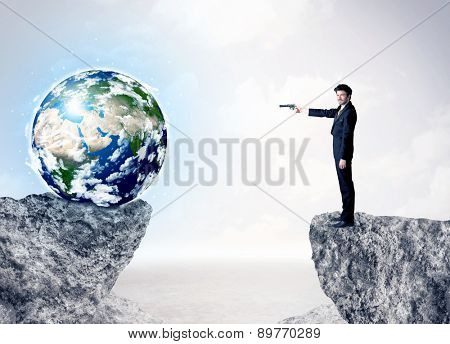 Businessman standing on the edge of mountain with a globe on the other side,