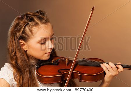 Half-face view of beautiful girl playing violin
