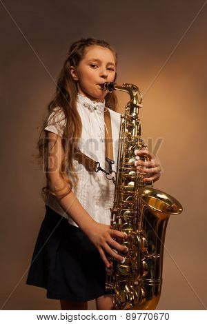 View of girl with long hair playing alto saxophone