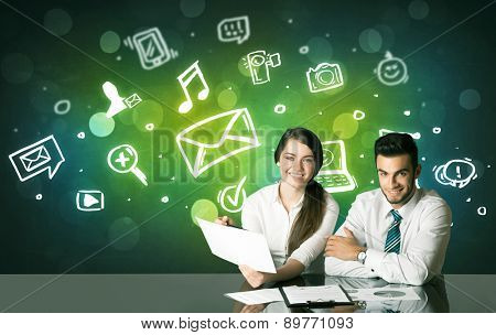 Business couple sitting at the black table with social media symbols on the background