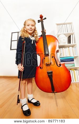 Small blond girl with curly hair holds cello