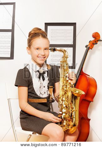 Happy girl in school dress with alto saxophone