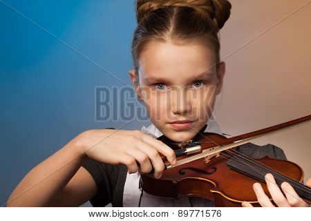 Beautiful girl close-up view playing on the violin