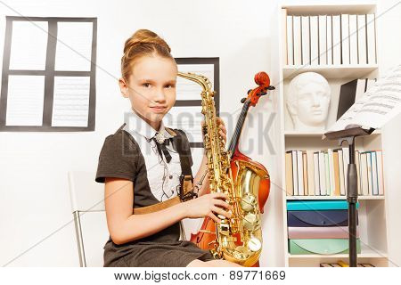 Cute girl in school uniform dress holds saxophone