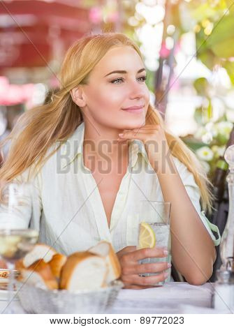 Portrait of cute blond female drink water with lemon in nice outdoor European cafe, healthy lifestyle, enjoying wonderful summer traveling to Italy
