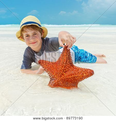 Boy and starfish on a tropical beach
