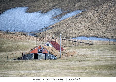 vintage traditional Icelandic farm houses in a valley surrounded by snow covered hills on the southern coast of Iceland during winter.