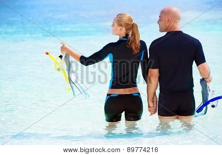 Back side of happy diver couple standing in the water and with wonder looking on side, enjoying extreme sport and active summer vacation