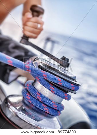 Holder of rope on sailboat, man pulling handle of spool, macro photo of yacht detail, working on water transport, luxury summer time sport