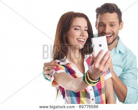 Happy hipster couple taking a selfie on white background