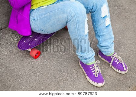 Teenager In Jeans And Gumshoes Sits On A Skateboard
