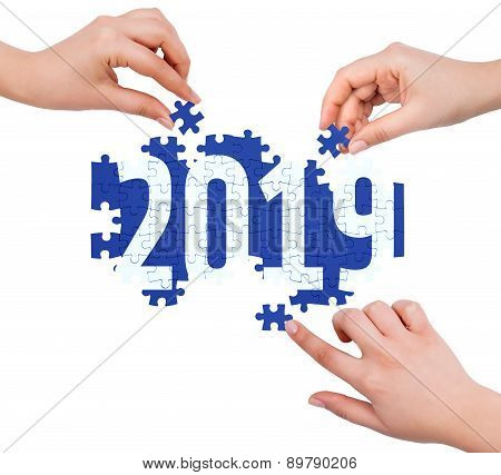Hands With Puzzle Making 2019 Word  Isolated On White