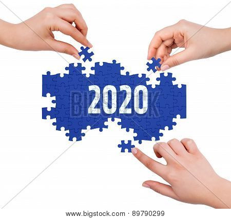 Hands With Puzzle Making 2020 Word  Isolated On White