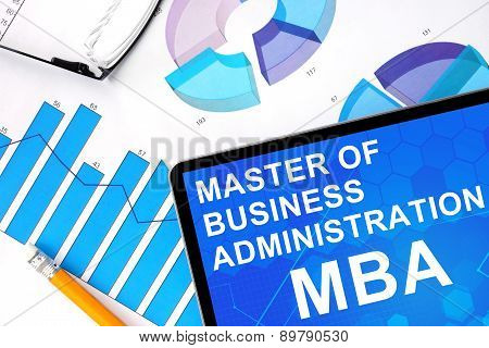 Tablet with word MBA - Master of Business Administration and graphs.