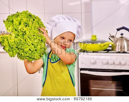 Child holding vegetable at kitchen.