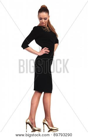 Side view of a beautiful young business woman looking down while holding her hands on the waist.