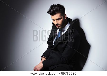 Picture of a young business man looking down while resting on a stool.