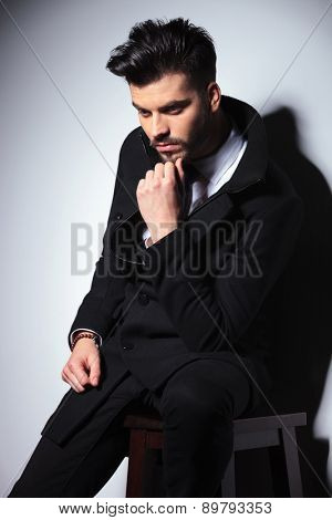 Side view picture of a young business man holding his hand to the chin, thinking while sitting on a chair.