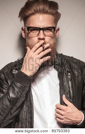 Close up portrait of a blond hipster business man smoking a cigarette while fixing his jacket.