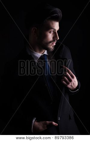Portrait of a young business man looking away from the camera while holding one hand in his pocket and fixing his collar.