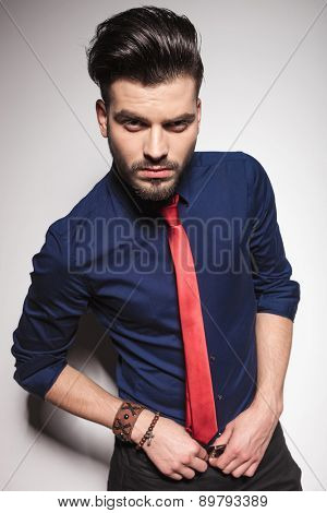 Attractive young business man holding both hands on his belt while looking at the camera.
