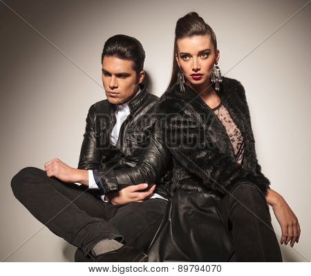 Beautiful fashion couple sitting together while looking away from the camera.