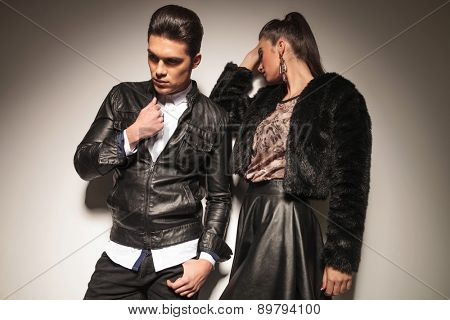 Fashion woman leaning on a wall while her lover is fixing his jacket.