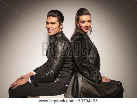 Young fashion couple posing back to back while sitting.