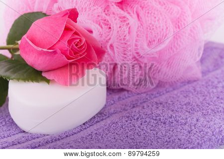 Soap with a pink rose on top of a purple towel, with a pink shower puff on background