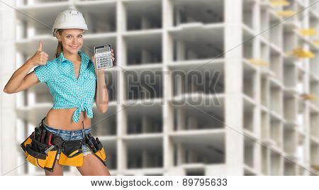 Young woman in hard hat holding calculator