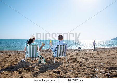 Portrait of a happy family in summer nature. Mother and father are sitting on a beach deck chair, da