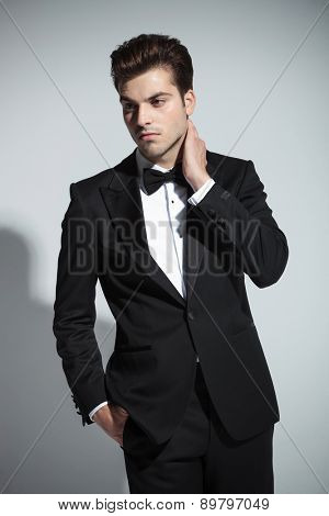Portrait of a young elegant business man holding his hand to his neck while looking away from the camera.