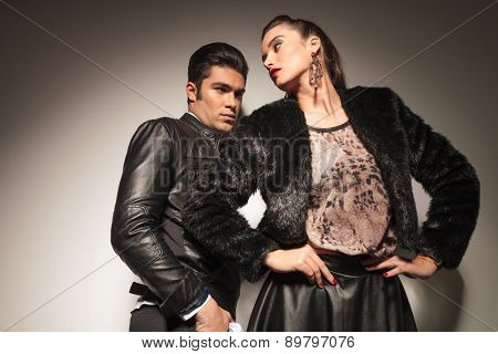 Sexy young fashion woman posing with her hands around her waist while her lover is leaning on a wall.