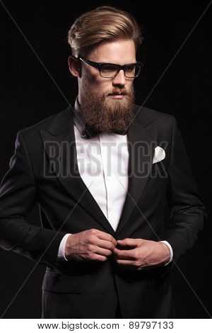 Picture of a elegant business man looking down while closing his jacket.