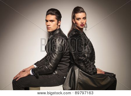 Fashion man and woman sitting back to back while holding their hands on the legs.