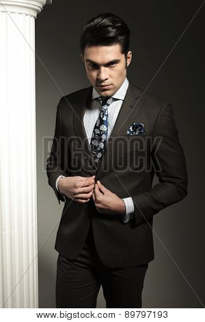 Handsome young business man closing his jacket while looking at the camera.