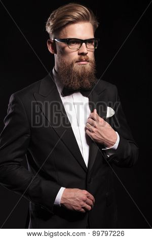 Portrait of a attractive young business man fixing his collar while looking away from the camera.