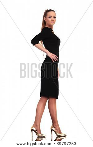 Side view of a elegant business woman walking on studio background, holding one hand on her waist while looking at the camera.