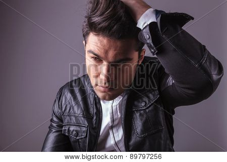 Close up picture of a casual fashion man fixing his hair while looking away from te camera.
