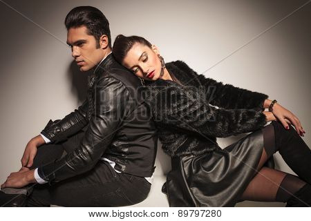 Sexy young fashion woman leaning her head on her lovers shoulder while he is sitting with his legs cossed.