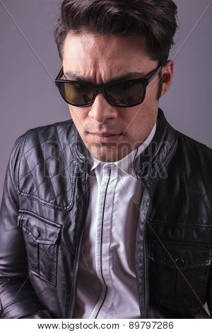 Close up picture of a casual fashion man wearing sunglasses, looking at the camera.