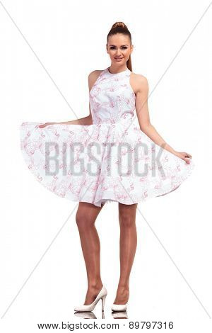Attractive young fashion woman standing on isolated background, holding her dress.