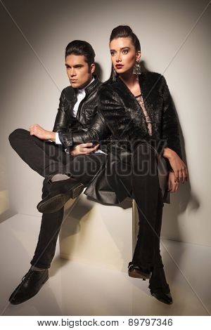 Full body picture of a fashion couple sitting together on a white table, both looking away from the camera.