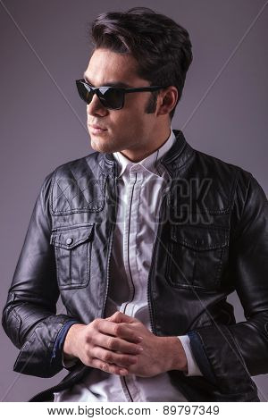 Portrait of a handsome fashion man looking away from the camera while holding his hands together.
