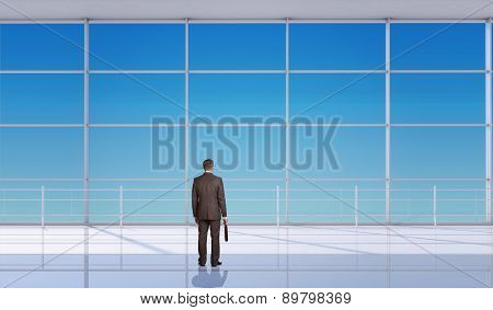 Businessman with suitcase in front of window