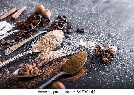 Chocolate powder cocoa and coffee spoons on the table black